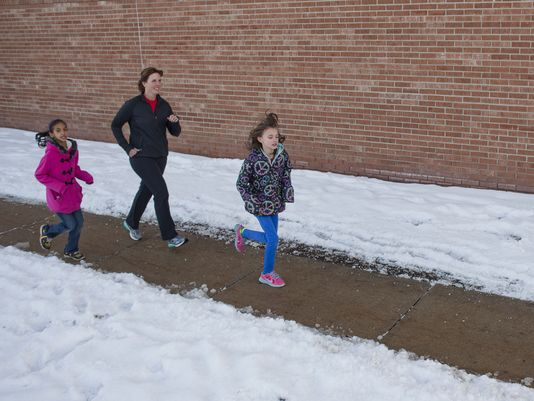 Shira Maydwell, 9, Dawn Schweihofer and Kendall Urie, 10, run laps around Cleveland Elementary School. (Tony Wittkowski | Times Herald)