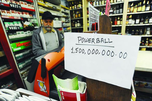 Baldev Singh, owner of the Mini Mart in St. Joseph, handles a Powerball lottery ticket purchase Tuesday afternoon. (Don Campbell | HP Staff)